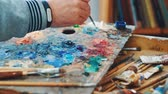 палетка : Artist mixes paints on the palette before painting a picture