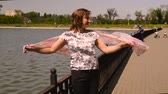 балерина : Young woman makes stretching exercise with dance elements on waterfront