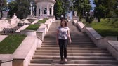 schody : Young woman descends stone stairs in a sity parck
