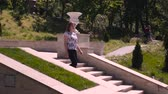 elmélkedő : Young woman descends stone stairs in a sity parck