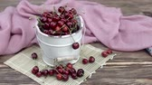 servir : Cherries in a white bowl on a wooden table.