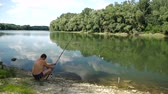 wędkarz : Fishing in river.A fisherman with a fishing rod on the river bank.