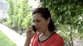 beszélő : Young attractive woman talking on mobile phone, outdoors
