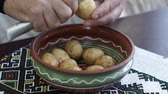 root vegetable dish : Peeling Potatoes in the home kitchen. A man holding a knife and peel the potatoes and clean in a bowl. Cooking food at home. Stock Footage