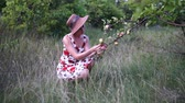 blondehair : Beautiful blonde girl in hat and dress standing on the apple garden.