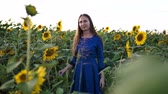 woman s day : beautiful girl in a dark blue dress on a field of sunflowers, smiling a beautiful smile, cheerful girl, style, lifestyle