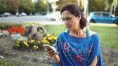 ás : Portrait of an Amazing Woman with a Smartphone Outdoors. Pretty Brunette Using Her Mobile Phone with Touch Screen Standing in the Park Stock Footage