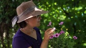 Portrait of a woman in a hat admire flowers in the garden.