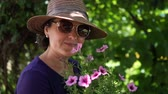 humanóide : Portrait of a woman in a hat admire flowers in the garden.