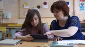 correspondência : Teacher at school uses digital tablet in classroom