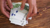 gyűjt : Man collecting and counting money euro bancnotes on table, hands close up.