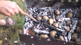 contrastes : hot coals in the sand with a stick man turns to a good baking potatoes