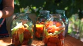 woman puts tomatoes in jar for preservation, preparation of canned vegetables
