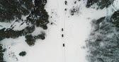 winter sports : The drone is flying over quad bikes driving through snow-capped mountains 4K Ultra HD