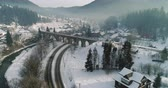 улица : Aerial view of a car passing under a railway bridge in a snow-covered village 4K Ultra HD