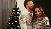 desfrutar : Happy young emotional couple posing on smart phone camera on christmas tree background.