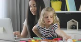 working parents : Caucasian woman with black long hair using laptop for working while her dauther sculpting from plasticine on home background.