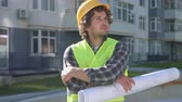 decking : Beautiful young builder with black curly hair in protective helmet and green vest holding drawing, composing his hands. Outdoor. Stock Footage