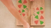 salami slice : Close up shot of man hands opening cardboard box with a large pizza on the floor at home. Stock Footage
