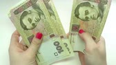 hryvnia : Close-up of a businessmans hands counting hundred  hryvnia bills at a table Stock Footage