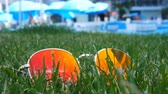 Sunglasses in the green grass. Reflections of the hotel and the beach near the sea. TimeLapse. Stock Footage