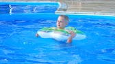 Little boy float on inflatable circle in the blue pool.