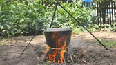 The pot of water hangs over the fire. The water boils. Close-up Stock Footage