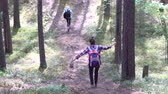 спуск : Tourists girls run down the hill in the woods