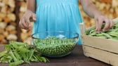 Young girl hands shelling peas into glass bowl, closeup - static camera