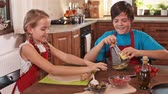 Kids at home making a pizza - stretching the dough and grating cheese
