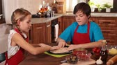 Kids at home making a pizza - stretching the dough with hands, camera slide