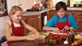 Kids at home making a pizza - stretching the dough with hands, and preparing ingredients