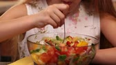 Young girl eating mixed vegetables salad - enjoying every bite, closeup, camera tilting