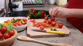 Child hands cutting cherry tomato for a vegetables salad - side view  of the cutting board at the kitchen sink