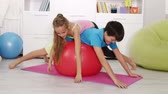 Boy and girl make a happy pile over large exercise rubber ball - relaxing after gymnastic