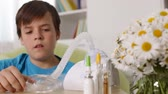 Boy using nebuliser inhaler with mask, allergy and asthma concept - rack focus, sliding camera