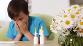 Boy with allergy blowing nose and sneezing - rack focus, sliding camera