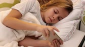 Young worried girl using smartphone texting in bed - camera slide