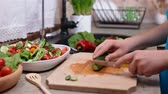 Child hands slicing a cucumber for a vegetables salad - side view  of the cutting board at the kitchen sink, camera slide