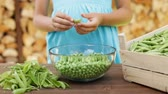 Young girl hands shelling peas into glass bowl, closeup - camera slide, track subject Wideo