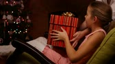 Young girl receiving kitten in a big gift box for christmas - sitting in rocking armchair by the fireplace