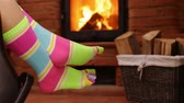 Woman feet hanging on rocking chair, swinging in front of fireplace - relaxing concept, static camera, closeup