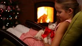 Young girl holding her christmas present by the fire - caressing a rescue adopted kitten, providing safety and comfort, sitting in rocking chair Wideo