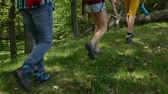 Hikers jumping over fallen tree log in the forest - teenagers and woman backpackers hiking in the woods, camera follows legs, closeup