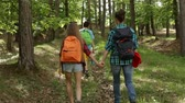 objevit : Hikers enjoy walking in forest - woman and teenagers walking uphill among trees - camera follows behind
