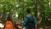Hikers walking downhill in a forest - woman and teenage girl enjoy the woods in summer