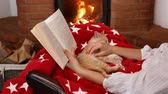 sallanan : Small kitten sleeping in woman lap in front of the fireplace - holidays season relaxation. Reading a book and watching the fire - camera slide, medium shot Stok Video