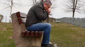 camarada : Man with walking stick on bench in the cemetery Stock Footage