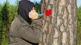 fabric : Angry man holding knife and fabric heart near the tree Stock Footage