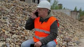 esmagado : Construction inspector with phone at the pile of crushed stone